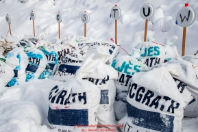 Musher food drop bags await the arrival of their owners in the afternoon at the McGrath checkpoint during the 2018 Iditarod race on Wednesday March 07, 2018. Photo by Jeff Schultz/SchultzPhoto.com  (C) 2018  ALL RIGHTS RESERVED