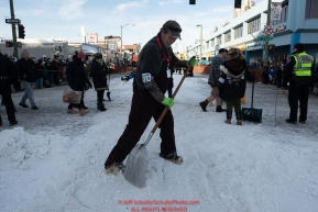 Volunteer trail maintenence crew Jim Lupton shovels snow at the C Street intersection during the ceremonial start of the 2019 Iditarod.Photo by Jeff Schultz/  (C) 2019  ALL RIGHTS RESERVED