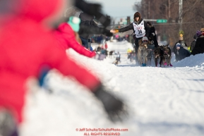 Robert Redington leans out to give high-fives on Cordova Street during the ceremonial start of the 2019 Iditarod in downtown Anchorage, Alaska on Saturday March 2.Photo by Jeff Schultz/  (C) 2019  ALL RIGHTS RESERVED