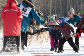 Youngster Kyde Friesen and family members give a high-five to musher Ryan Santiago during the ceremonial start of the 2019 Iditarod in midtown Anchorage, Alaska on Saturday March 2.Photo by Jeff Schultz/  (C) 2019  ALL RIGHTS RESERVED