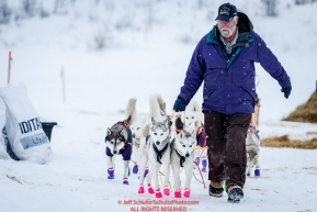 Volunteer Chris Kelley leads Rob Cook's team as he leaves at the ghost-town checkpoint of Iditarod on Saturday, March 10th during the 2018 Iditarod Sled Dog Race -- AlaskaPhoto by Jeff Schultz/SchultzPhoto.com  (C) 2018  ALL RIGHTS RESERVED