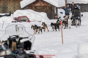 Tom Knolmayer runs down the street and into the Kaltag village checkpoint on Sunday afternoon March 11th during the 2018 Iditarod Sled Dog Race -- AlaskaPhoto by Jeff Schultz/SchultzPhoto.com  (C) 2018  ALL RIGHTS RESERVED