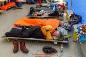 Linwood Fiedler and other mushers get some rest on cots inside the community center at the Kaltag village checkpoint on Sunday morning March 11th during the 2018 Iditarod Sled Dog Race -- AlaskaPhoto by Jeff Schultz/SchultzPhoto.com  (C) 2018  ALL RIGHTS RESERVED