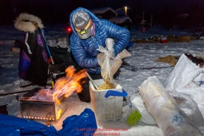 Jessie Royer prepares her dog's meal at the Kaltag village checkpoint on Sunday morning March 11th during the 2018 Iditarod Sled Dog Race -- AlaskaPhoto by Jeff Schultz/SchultzPhoto.com  (C) 2018  ALL RIGHTS RESERVED