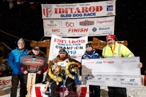 Pete Kaiser sits with his lead dogs Marrow (L) and Lucy and the principal sponsors at the Nome finish line after winning the 2019 Iditarod Trail Sled Dog Race. Pete's winning time is 9 days 12 hours 39 minutes and 6 secondsPhoto by Jeff Schultz/  (C) 2019  ALL RIGHTS RESERVED