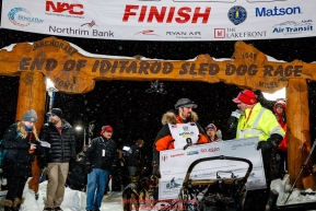 Pete Kaiser recieves his winning check, albeit blank, from GCI representive Bob James at the Nome finish line after winning the 2019 Iditarod Trail Sled Dog Race. Pete's winning time is 9 days 12 hours 39 minutes and 6 secondsPhoto by Jeff Schultz/  (C) 2019  ALL RIGHTS RESERVED