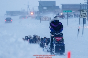 Jessie Royer runs down Front Street with a police escort in a wind-storm as she makes her way toward the Nome finish line to place 3rd in the 2019 Iditarod sled dog race.Photo by Jeff Schultz/  (C) 2019  ALL RIGHTS RESERVED