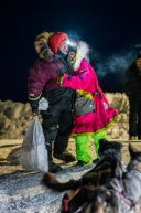 Veteran musher Dee Dee Jonrowe greats Aaron Burmeister with a hug upon his arrival in Ruby, Alaska on March 13, 2020.