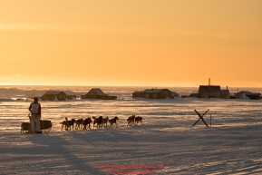 Matt Failor runs past fish camp shacks and a tripod trail marker on the trail heading toward the finish at Nome on Wednesday March 14th during the 2018 Iditarod Sled Dog Race.  Photo by Jeff Schultz/SchultzPhoto.com  (C) 2018  ALL RIGHTS RESERVED