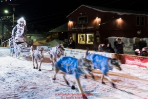 Nick Petit runs down the chute at the finish line in Nome, Alaska early on Wednesday morning March 14th as places 2nd in the 46th running of the 2018 Iditarod Sled Dog Race.  Photo by Jeff Schultz/SchultzPhoto.com  (C) 2018  ALL RIGHTS RESERVED