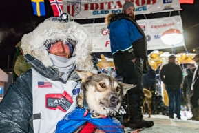 Nick Petit poses at the finish line in Nome, Alaska with his lead dog Libby early on Wednesday morning March 14th as places 2nd in the 46th running of the 2018 Iditarod Sled Dog Race.  Photo by Jeff Schultz/SchultzPhoto.com  (C) 2018  ALL RIGHTS RESERVED