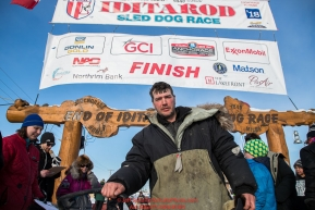 Ray Redington Jr. poses at his sled at the Nome finish line on Wednesday March 14th in the 46th running of the 2018 Iditarod Sled Dog Race.  Photo by Jeff Schultz/SchultzPhoto.com  (C) 2018  ALL RIGHTS RESERVED