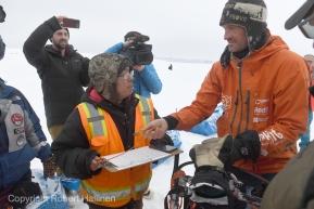 Kermit Ivanoff checks in Thomas Waerner at the Unalakleet, AK Iditarod checkpoint  in first place on Sunday, March 15, 2020. (Photo by Bob Hallinen)