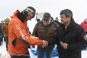 Thomas Waerner accepts the Ryan Air first to the coast award from Allen Ivanoff at the Unalakleet, AK Iditarod checkpoint after arriving in first place on Sunday, March 15, 2020. The award is $2,000 worth of gold nuggets. In the middle is race marshal Mark Nordman. (Photo by Bob Hallinen)
