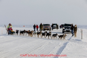 Monica Zappa on the trail just a few miles from the finish line crosses the road as spectators cheer her on as she nears Nome on Saturday March 15 during the 2014 Iditarod Sled Dog Race.PHOTO (c) BY JEFF SCHULTZ/IditarodPhotos.com -- REPRODUCTION PROHIBITED WITHOUT PERMISSION