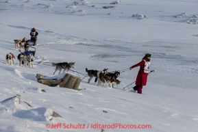 Lisbet Norris leads her team to the trail just outside Nome on  the Bering Sea with Marcelle Fressineau behind her on Saturday March 15 during the 2014 Iditarod Sled Dog Race.PHOTO (c) BY JEFF SCHULTZ/IditarodPhotos.com -- REPRODUCTION PROHIBITED WITHOUT PERMISSION