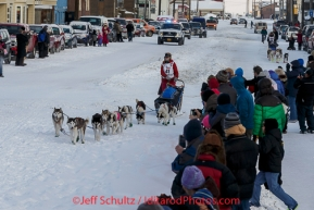 Lisbet Norris leads Marcelle Fressineau into the finish chute to claim 48th place at Nome on Saturday March 15 during the 2014 Iditarod Sled Dog Race.PHOTO (c) BY JEFF SCHULTZ/IditarodPhotos.com -- REPRODUCTION PROHIBITED WITHOUT PERMISSION