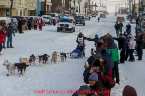 Marcelle Fressineau runs into the finish chute to claim 49th and last place at Nome on Saturday March 15 during the 2014 Iditarod Sled Dog Race.PHOTO (c) BY JEFF SCHULTZ/IditarodPhotos.com -- REPRODUCTION PROHIBITED WITHOUT PERMISSION