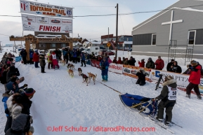 Marcelle Fressineau runs into the finish chute to claim 49th and last place at Nome as Lisbet Norris arrived just a minute before her on Saturday March 15 during the 2014 Iditarod Sled Dog Race.PHOTO (c) BY JEFF SCHULTZ/IditarodPhotos.com -- REPRODUCTION PROHIBITED WITHOUT PERMISSION