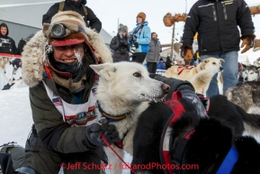 Marcelle Fressineau gives her lead dog a hug in the finish chute shorlty after finishing in 49th and last place at Nome on Saturday March 15 during the 2014 Iditarod Sled Dog Race.PHOTO (c) BY JEFF SCHULTZ/IditarodPhotos.com -- REPRODUCTION PROHIBITED WITHOUT PERMISSION