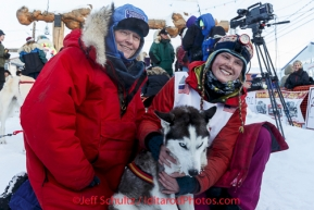 Lisbet Norris gives her lead dog Ruby a hug in the finish chute shorlty after finishing in 48th at Nome.  With her is her mother Kari Skogen who ran her first race 30 years ago. Saturday March 15 during the 2014 Iditarod Sled Dog Race.PHOTO (c) BY JEFF SCHULTZ/IditarodPhotos.com -- REPRODUCTION PROHIBITED WITHOUT PERMISSION