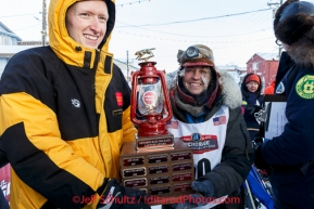 Wells Fargo Bank Nome store manager, Tyler Hull, presents Marcelle Fresineau with the red lantern last place award at the finish line shorlt after she finished in 49th place on Saturday March 15 during the 2014 Iditarod Sled Dog Race.PHOTO (c) BY JEFF SCHULTZ/IditarodPhotos.com -- REPRODUCTION PROHIBITED WITHOUT PERMISSION