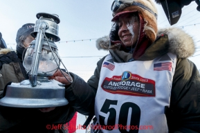 Marcelle Fressineau extinguishes the widow's lamp signifying the last musher is off the trail shorlty after she came in last and 49th place into Nome on Saturday March 15 during the 2014 Iditarod Sled Dog Race.PHOTO (c) BY JEFF SCHULTZ/IditarodPhotos.com -- REPRODUCTION PROHIBITED WITHOUT PERMISSION