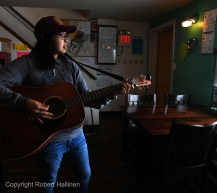 Andrea Irrigoo sings plays her guitar, Dutches from Dutch, at the Pingo Bakery Seafood House in Nome AK Iditarod as people wait for the first Iditarod team to arrive on Monday, March 16, 2020. Irrigoo learned to play her guitar while working at a crab processing plant in Kodiak thus the name. (Photo by Bob Hallinen)