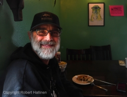 Mark Sass has a cinnamon roll at the Pingo Bakery Seafood House in Nome AK as he waits for his son Iditarod musher Brent Sass to arrive on Monday, March 16, 2020. (Photo by Bob Hallinen)