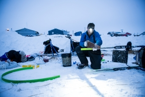 Jason Campeau, changing his sled runner plastic early morning to head up the coast to Nome, March 16th, 2020.