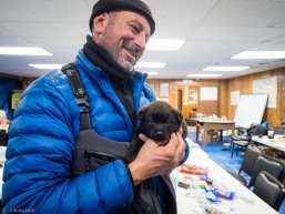 A snow machiner travelling the Iditarod trail meets a local puppy in Koyuk, AK on March 17, 2020.