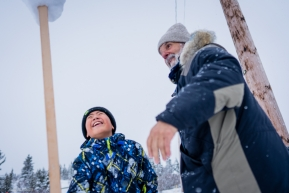 Bill Sampson, a Koyuk checkpoing veterinarian, and a yound Koyuk resident play at balancing snow on a stick.  March 17, 2020