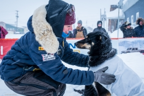 One of Jeff Deeter's dogs gets an embrace by family after completing the Iditarod on March 18, 2020.