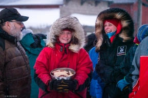 Aily Zirkle's family members chat with Mark Nordman of the Iditarod with fresh dog treats in hand.