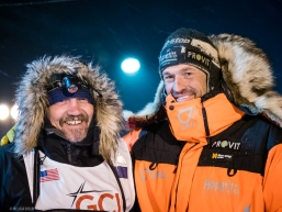 Tom Frode Johansen is greeted by Qrill teammate and Iditarod winner Thomas Waerner after crossing the finish line in the early hours of March 19, 2020 (Nome, AK).