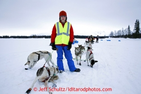 A volunteer holds onto Wade Marr's team at the Finger Lake checkpoint March 4, 2013.