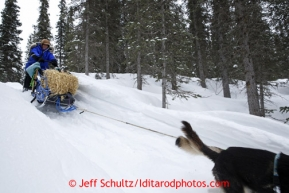 Karin Henrickson leaves with a bale of hay on her seld near Finger Lake checkpoint March 4, 2013.