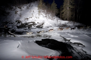 Justin Savidas crosses an ice bridge over Dalzell Creek in the night during the 2013 Iditarod sled Dog Race   March 4, 2013.  Photo by Jeff Schultz Do Not Reproduce without permission