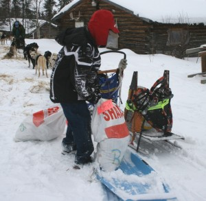 This young helper in Shageluk lifts a drop bag off the blue toboggan.