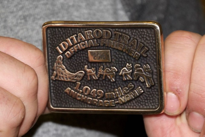 Patrick Beall displays the Belt Buckle awarded to rookies in Nome